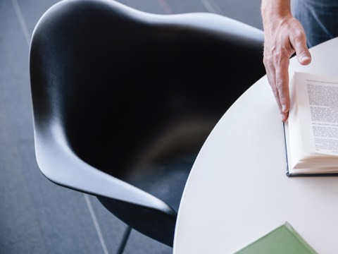 Hands flip the pages of a book that rests on a table served by a black Eames Molded Plastic Chair.