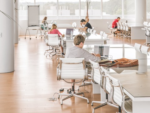 Five college students, all sitting in white Eames Aluminum Group Chairs, work individually in a large study room.