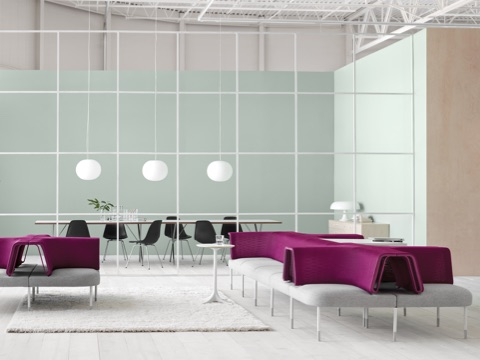 Gray and magenta Public Office Landscape seating adjacent to a glass-walled meeting room containing Eames Molded Plastic Chairs.