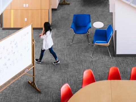 A college student walks through an interaction space featuring Swoop Plywood Lounge Chairs and Eames Molded Plastic Chairs.