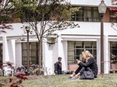 A female college student checks her smartphone while sitting on the grass outside an academic building.