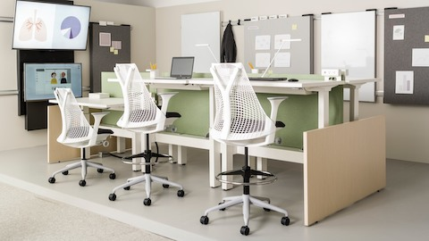A learning space featuring height-adjustable tables paired with two white Sayl Stools and one white Sayl Chair.