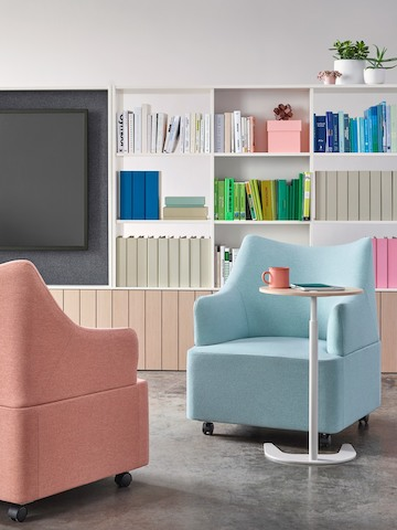 Two Plex club chairs with salmon and light blue upholstery face each other with a height-adjustable work table between.