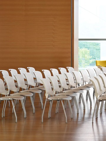 Four rows of white Caper Stacking Chairs in a learning space.