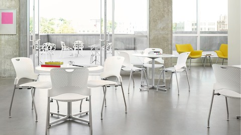 A student gathering space with floor-to-ceiling windows, white Caper Stacking Chairs, and yellow Swoop Lounge Chairs.