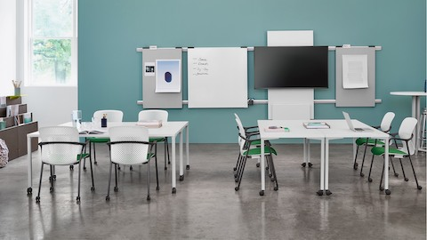 A classroom featuring white Everywhere Tables, white Keyn side chairs with green seat pads, and Metaform Portfolio blocks.