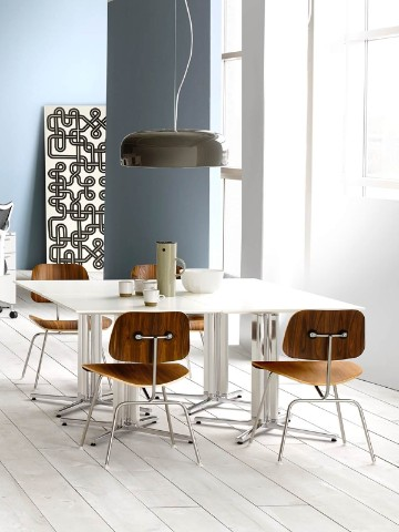 Four Eames Molded Plywood Chairs surround white Everywhere Tables in a break area.