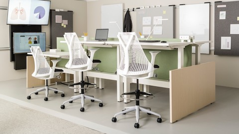 Sayl chairs and stools with white frames and black seats, paired with height-adjustable tables in a healthcare benching application.