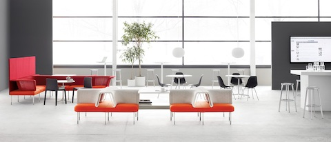 An open collaboration area featuring Social Chairs from the Public Office Landscape system in orange, red, and white.