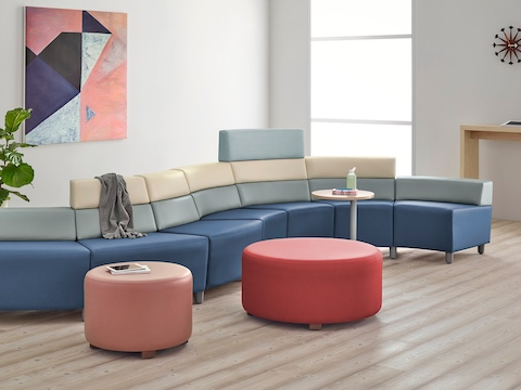 A curved configuration of the Steps Lounge System, featuring modules of blue, light gray and beige with varying back heights.