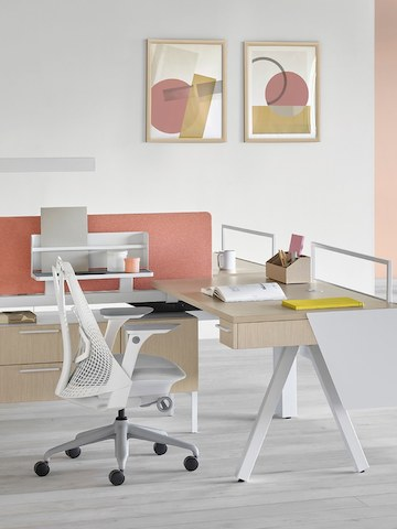 A Canvas Vista desk with a white base and ash surface with a pink tackable screen and a Sayl office chair with a white back and gray base.