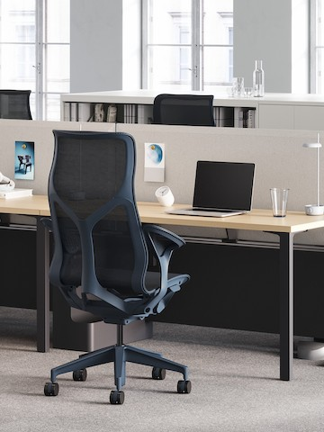 A dark blue Cosm high-back chair at a Canvas workstation with a graphite base, ash surface, and a tackable screen in gray.