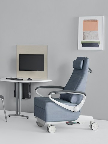 A light blue Ava patient chair with a Mora System peninsula on the side wall in an exam room setting.