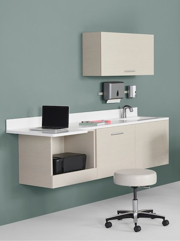 Mora System casework in an ash finish with a white solid surface top and sink. The casework is wall-hung and has an upper storage cabinet and lower storage cabinets, including a technology cabinet.