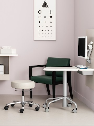 An exam room with Intent Solution wall unit holding a monitor on a Flo monitor arm and a mobile height adjustable table, with a Physician Stool, and a lounge chair.