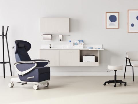 Exam room with a dark blue Ava Recliner and an Intent Solution mobile, height-adjustable table and wall unit to the side with a Physician Stool and Verus Side Chair in a light gray upholstery and black frame with Mora casework in a light wood laminate on the wall in the background.