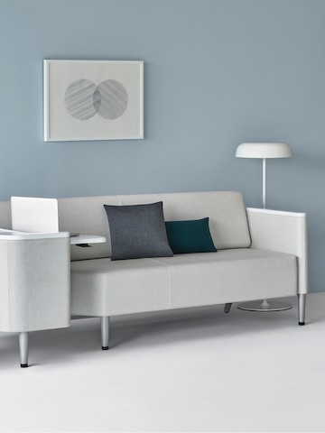 A Palisade Flop Sofa in light gray textile with white solid surface arm caps and white adjustable table with Durawrap top.