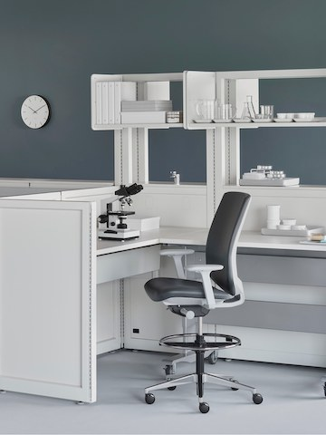 A medical laboratory setting containing Co/Struc System with a height-adjustable process table and a dark gray Verus Stool.
