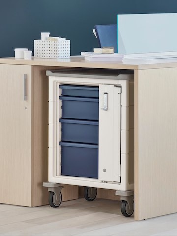 A Procedure and Supply Cart with keyless lock and blue drawers in a storage cove within an Ethospace Nurses Station.