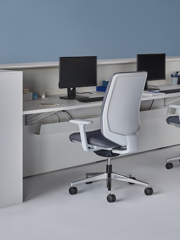 An interior view of a prefab Commend Nurses Station with a white work surface, white Corian transaction surfaces, Verus Chairs, and monitor stands.