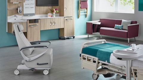 A patient room with a bed, recliner, guest sofa, and Compass System modular storage.