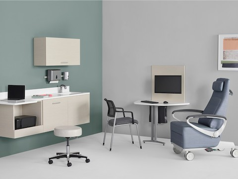 An exam room setting with Mora System casework on the wall in a light wood finish and a Mora peninsula on the side wall located between an Ava patient recliner and a Verus Side Chair.