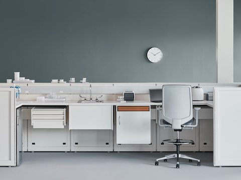 A laboratory setting featuring a white Co/Struc System with below-surface storage and a gray Verus Stool in a medical laboratory.