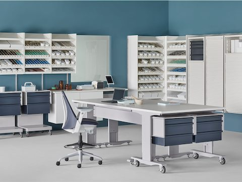 A pharmacy setting with a white Co/Struc System containing dispensing shelves, lockers, process tables, L Carts with blue drawers, and a Sayl Stool.