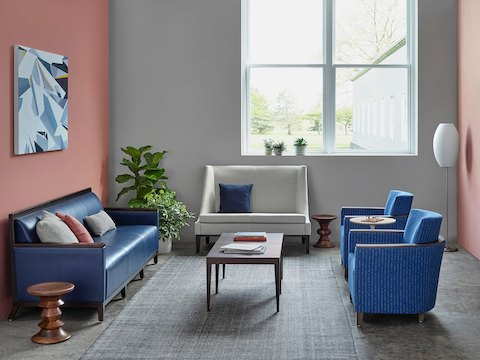 Eames Walnut Stools complement blue and gray lounge seating in a healthcare sitting area.