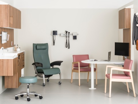 An exam room containing a patient recliner, caregiver stool, two side chairs, and wall-hung storage from the Compass System.
