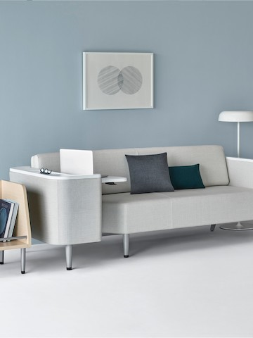 A patient room with a Palisade Flop Sofa in light gray upholstery with a Palisade Tote on one side and an Ode floor lamp on the other side.