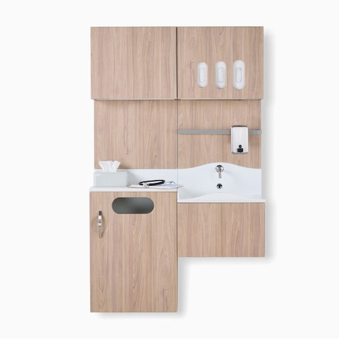 A Compass System casework wall unit in a medium elm wood laminate finish with integrated waste receptacle, white solid surface sink, and upper storage for gloves.