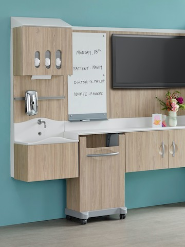 A patient room environment with a Compass System footwall in a light wood finish.