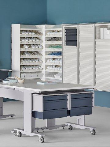 A pharmacy environment with a Co/Struc System dispensing system, storage lockers, and process tables.