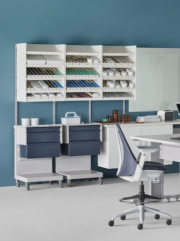 A pharmacy environment with a Co/Struc System dispensing system, L Carts, and a Sayl Stool.