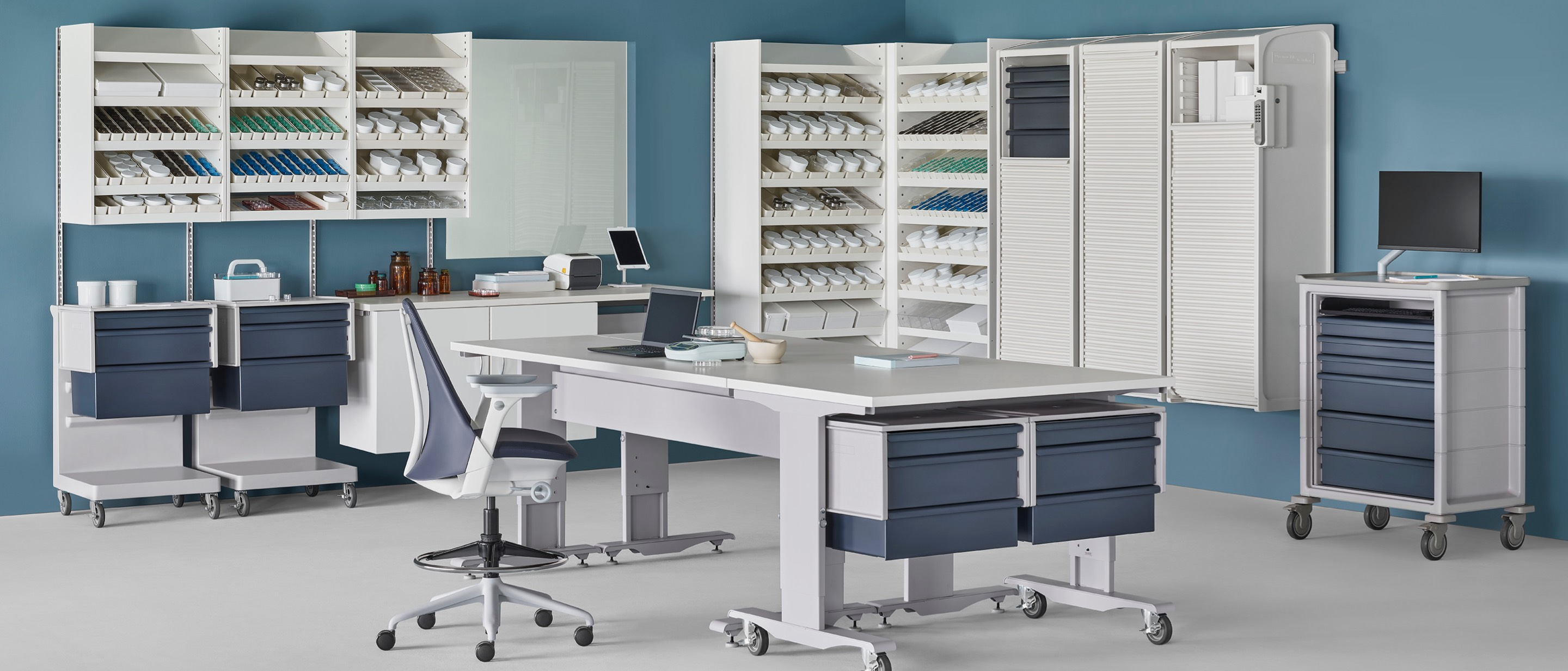 A pharmacy environment containing a Co/Struc System of dispensing shelves, lockers, process tables, L Carts with blue drawers, a technology cart with blue drawers, and a Sayl Stool.
