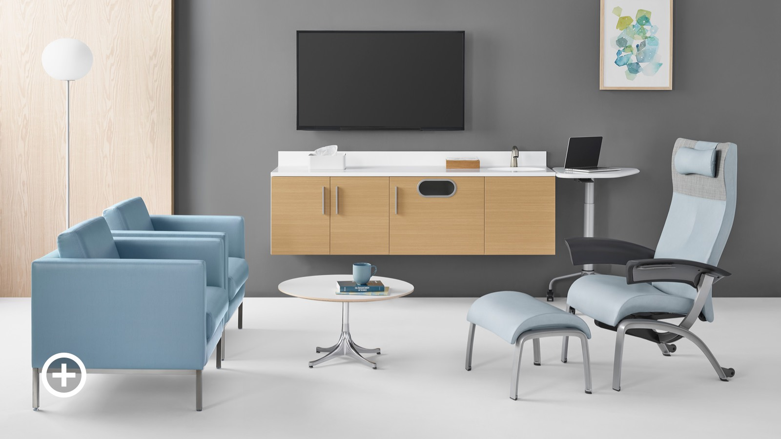 An exam room set up for consultation with Mora System casework and  an Intent mobile, height adjustable table on the back wall, two Riva lounge chairs facing a Nala patient chair and a Nelson occasional table between.
