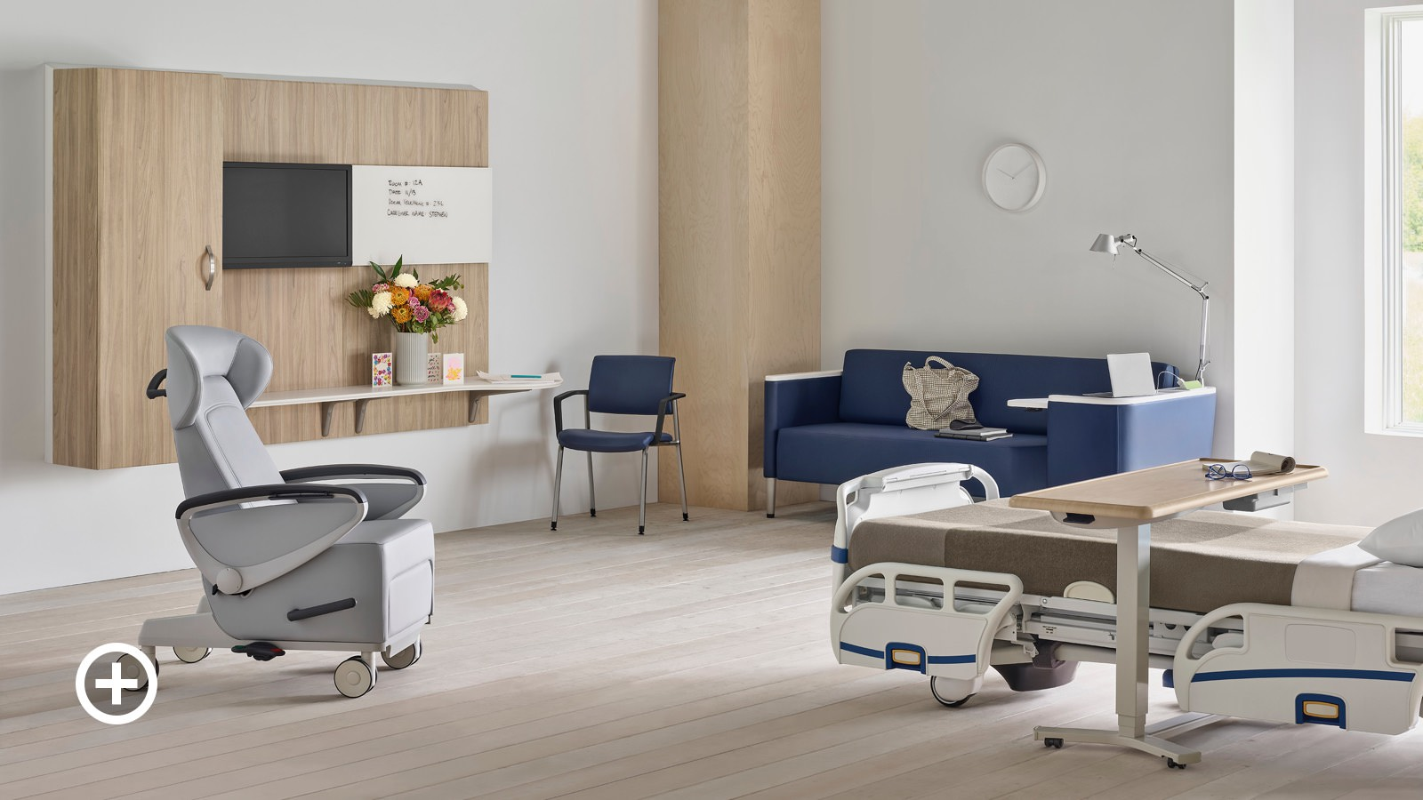 Compass System footwall in a patient room with a gray Ava patient recliner, a blue Palisade Flop Sofa, a fully-upholstered blue Verus Side Chair, and a Mirage Overbed Table over a hospital bed.