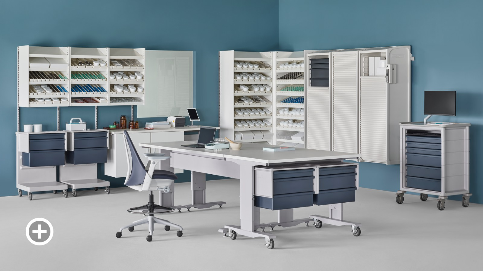 A pharmacy containing a white Co/Struc System of dispensing shelves, lockers, process tables, L Carts with blue drawers, a technology cart with blue drawers and a Sayl Stool.