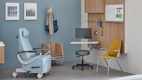 An exam room featuring Compass System to support technology and equipment, and a blue Ava Recliner.