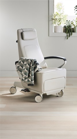 Three-quarter, right view of a light gray Ava Recliner with a blanket draped over the arm.
