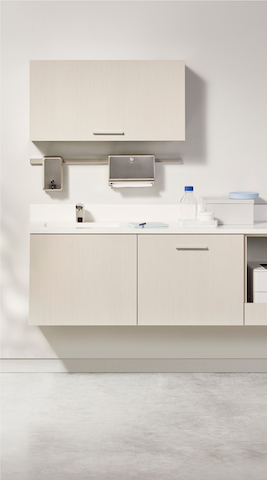 Exam room with Intent mobile table in a white top and silver base finish and wall unit in ash finish with a silver monitor arm holding a monitor. A Verus Side Chair in dark blue upholstery and a black frame. A physician's stool in a soft white upholstery and a black base.