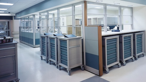 Six mobile healthcare storage carts with casters and blue drawers positioned next to a glass-walled work area.
