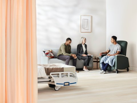 Patient Room with Compass footwall in a medium walnut with a family member and physician sitting on a light gray Pamona Flop Sofa talking with a patient sitting in a dark green Sahara recliner.