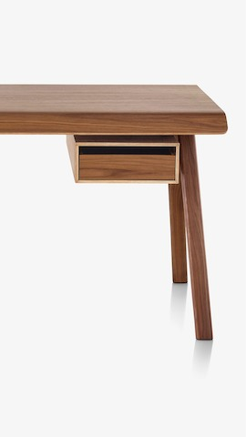 Partial view of a Distil Desk with a medium woodgrain finish. Select to see desks available from the Herman Miller Store.