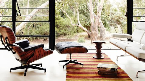 A residential lounge with an Eames Lounge Chair and Ottoman and Eames Sofa. Select to learn about designers Charles and Ray Eames.