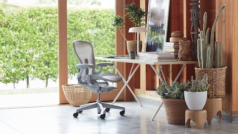 A home office with an Aeron Chair and Nelson X-Leg Table. Select to see office chairs available from the Herman Miller Store.