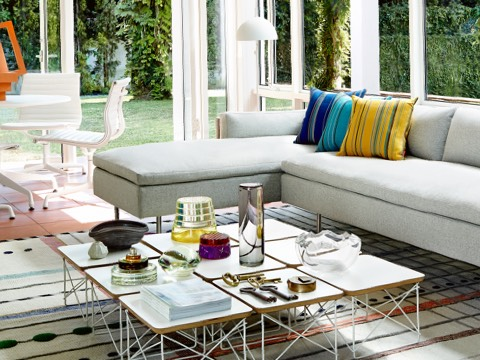 A residential setting with floor-to-ceiling windows, a gray Bolster Sofa, and nine Eames Wire Base Low Tables with white tops.