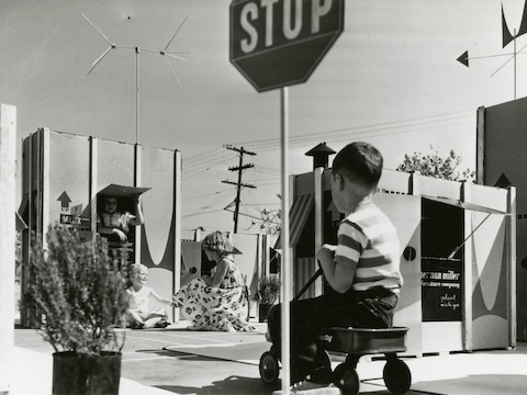 A vintage photo of children playing among large cartons.