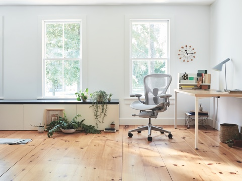 Aeron Chair in mineral seen from the front next to an Everywhere Table in a brightly lit home setting.